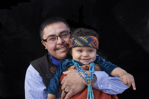 A photo of a young Navajo man and his child.