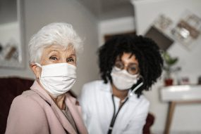 A photo of an older woman and her doctor.