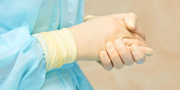A photo of a person's hands showing gloves and gown.