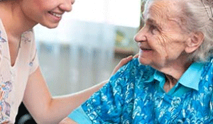 Photo: A caregiver and older woman in an assisted living facility