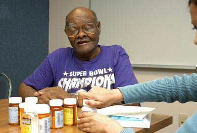 A photo of an older man on multiple medications participating in a medication review.