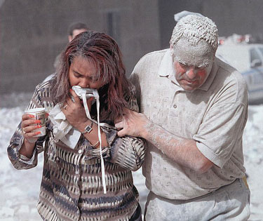 A photo of a man covered with dust assisting a woman after the 911 World Trade Tower attack.
