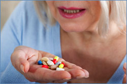 A photo of a woman with a handful of pills.