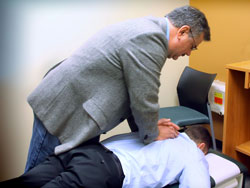 A chiropractor demonstrating an adjustment on the patient's thoracic spine.