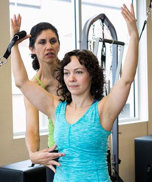 Pilates teacher instructing a women in exercise.
