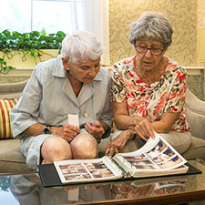 A photo of 2 women looking at personal photos.